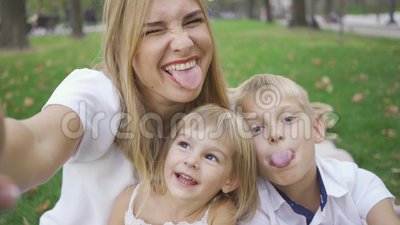 Kobieta z kaukaską i jej dzieci patrzące na uśmiech kamery Kobieta zabierająca selfie z dziećmi Mały chłopak, dziewczynka i zbiory