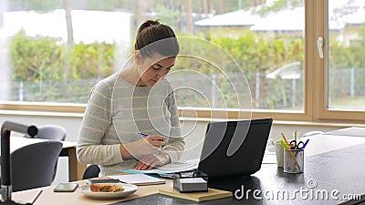 Kobieta z laptopem i papierami pracuje w domu zbiory