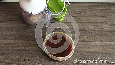 Kobieta zamyka dekiel blender puchar i mleje arachidy i ziarna dla robić halva Obok zbiornika jest miodowy dodawać zdjęcie wideo