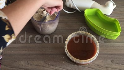 Kobieta zamyka dekiel blender puchar i mleje arachidy i ziarna dla robi? halva Obok zbiornika jest miodowy dodawa? zbiory wideo
