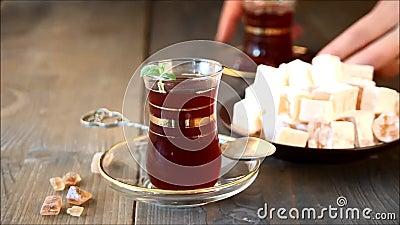 Kobiety ręka stawia tureckiej herbaty w tradycyjnej szklanej filiżance na drewnianym stole oriental zdjęcie wideo