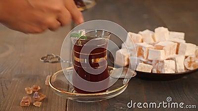 Kobiety ręka stawia tureckiej herbaty w tradycyjnej szklanej filiżance na drewnianym stole oriental zbiory