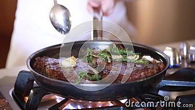 Kock som non steker stödögonbiffar med smörvitlök och rosmarin i pinnepanna stock video