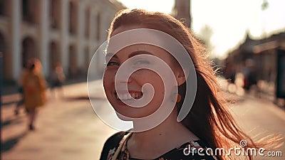 Koel redhair met sproetenvrouw in midden van de stad Blazende wind Zonsondergangverlichting stock video