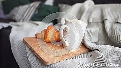 Koffie in een witte beker en een verse croissant op een luie sofa Ontbijten op een koude winterdag Het begrip comfort stock footage
