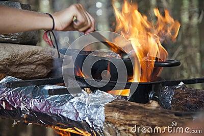 Kokend diner op kampvuur