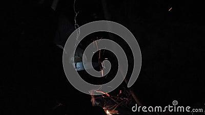 Kokend in gebiedsvoorwaarden bij nacht, kokende pan bij het kampvuur stock video