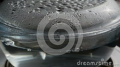 Kokend water in transparante glassteelpan met condensatie stock video