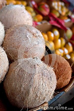 Kokosnötter och annan frukt på skärm på bondemarknaden