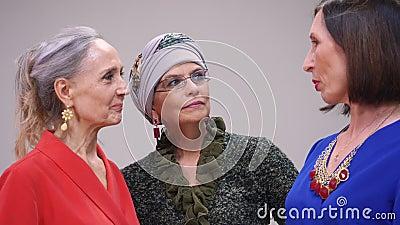 Komt volwassen vrouw drie die over iets spreken terwijl vriendschappelijk samen Gelukkige vrouwenvrienden die op vergadering rodd stock videobeelden