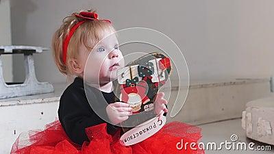 Koncepcja świąteczna - mała dziewczynka bawiąca się zabawką z 'MERRY CHRISTMAS' napisała na niej w języku rosyjskim zdjęcie wideo