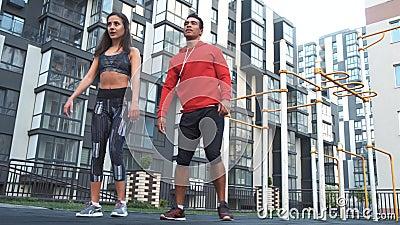 Kondition, sport, öva och sunt livsstilbegrepp - man och kvinna som utomhus gör squats i stad arkivfilmer