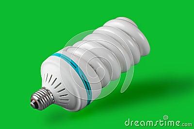 Ökonomische Glühlampe, die auf grünem Hintergrund steht