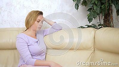 Konzept des Gef?hls Traurige Frau, die auf Sofa im Wohnzimmer sitzt stock footage