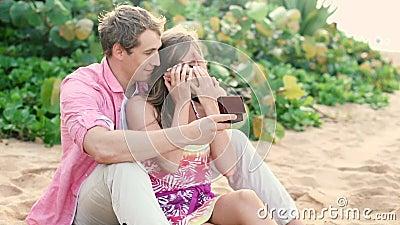 Koppla ihop förälskat, mannen som förvånar hans partner med förlovningsringen på stranden arkivfilmer