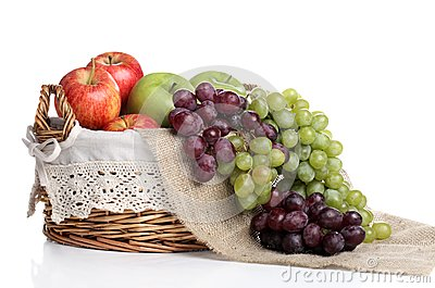 Korg full av äpplen och saftiga druvor