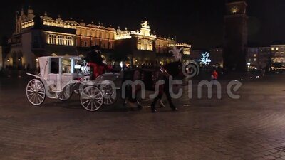 Old-fashioned Horse drawn carriages at Rynek Glowny square in Krakow, Poland stock footage