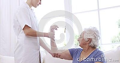 Krankenschwester, die den Arm der älteren Frau überprüft stock video