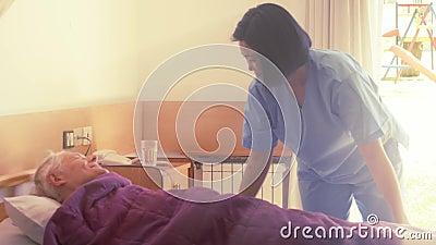 Krankenschwester hilft älteren Männern, die im Krankenhaus schlafen gehen stock video
