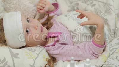 KRANKES MÄDCHEN MIT FIEBER Ein Kind mit Fieber liegt im Bett und isst Frucht stock video