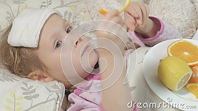 KRANKES MÄDCHEN MIT FIEBER Ein Kind mit Fieber liegt im Bett und isst Frucht stock video footage