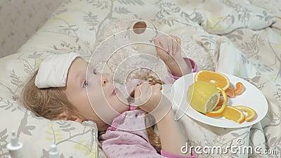 KRANKES MÄDCHEN MIT FIEBER Ein Kind mit Fieber liegt im Bett und isst Frucht stock footage