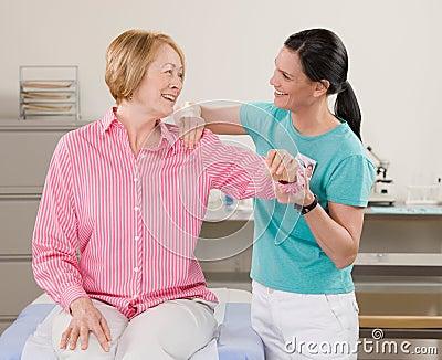 Körperlicher Therapeut, der womans Schulter überprüft