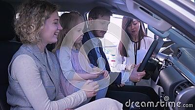 Kupienie rodzina transport, potomstwa dobiera si? z ?licznym dzieciakiem dziewczyna komunikuje o zakupu samochodzie z sprzedawcy  zdjęcie wideo