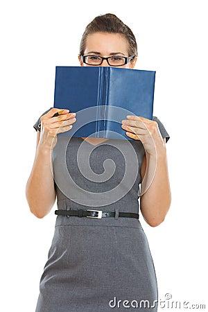 Kursteilnehmerfrau, die hinter Notizbuch sich versteckt