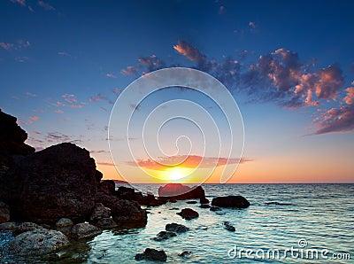 Kust över stenig solnedgång