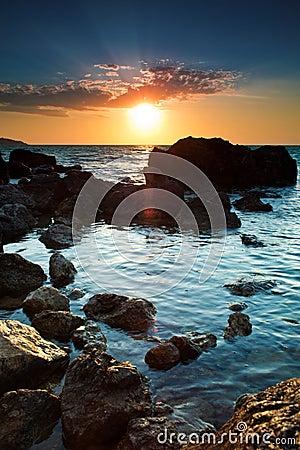 Kustlinje över stenig solnedgång