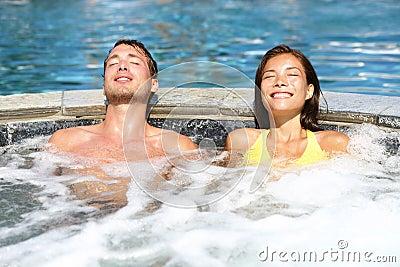 Kuuroordpaar die genietend Jacuzzi van hete ton ontspannen