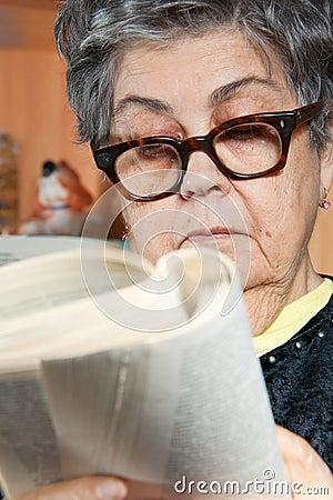 Kvinna för pensionär för bokståendeavläsning