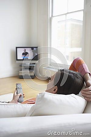 Kvinna på hållande ögonen på TV för soffa