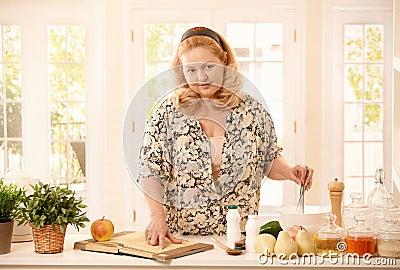 Kvinna som kontrollerar recept i kök