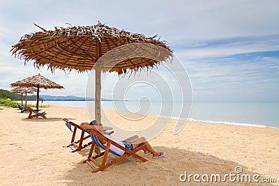 Kvinna som tycker om ferier under ett slags solskydd