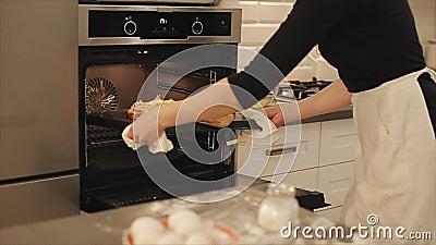 Kvinnan får pizza in i den svarta ugnen casserole som lagar mat läckert home hemlagat recept arkivfilmer