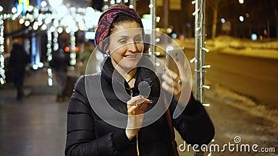 Kvinnan i frisk nattetid av dagklockor något som är gladlynt, som lyftte hennes envishet i telefonen lager videofilmer
