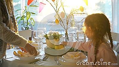 Kvinnan och hennes lilla dotter ställer in easter den festliga tabellen med kanin- och ägggarnering stock video