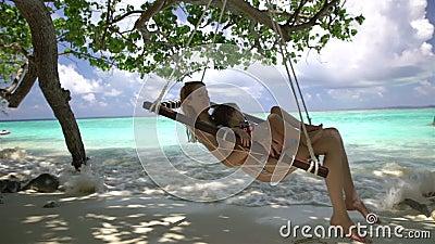 Kvinnan och hennes lilla dotter tycker om en vila i en hängmatta på den tropiska stranden lager videofilmer