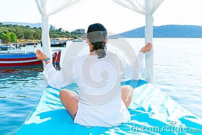Kvinnan på meditationen på havet seglar utmed kusten,
