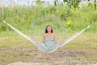 Kvinnan sitter på hängmattan i parken