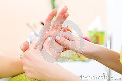 Kvinnan spikar in massage för salonghälerihand