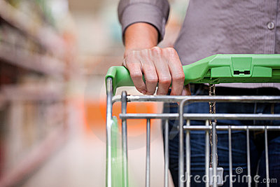 Kvinnashopping på supermarketen med trolleyen