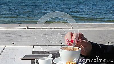 Kvinnlig hand som r?r kaffe med en tesked i ett utomhus- kaf? arkivfilmer