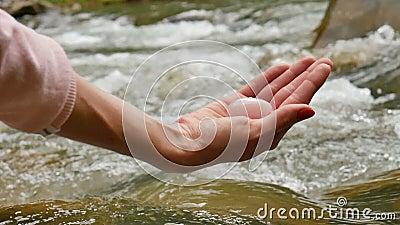 Kvinnlig hand som rymmer ett rosa ägg för yoni för kvartskristall på flodbakgrund Kvinnors hälsa, enhet med naturbegrepp stock video