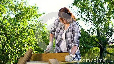 Kvinnlig snickare med skyddande exponeringsglas på att göra träjobb i sommarträdgård lager videofilmer