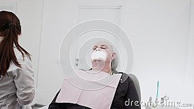 Kvinnlig tandläkare som utför prov och kirurgiska ingrepp med steriliserad utrustning Den manliga patienten i tandstolen arkivfilmer