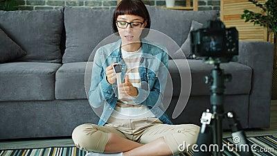 Kvinnliga bloggare som spelar in video om digitaltittare med kamera i lägenhet arkivfilmer