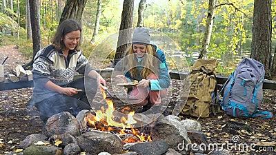Kvinnliga vänner lagar traditionella pannkakor över en öppen brand i lägret utomhus under en hike stock video